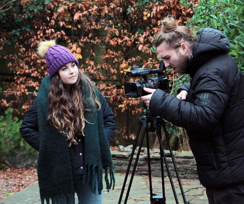 Tess and freelance cameraman filming content outdoors in autumn for client projects